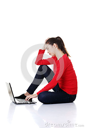 Sad woman looking on laptop screen.
