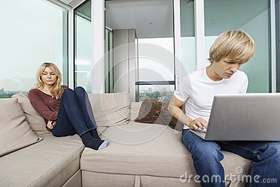 Sad woman beside man using laptop in living room at home