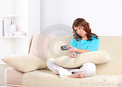 Sad woman sitting on sofa with remote controller