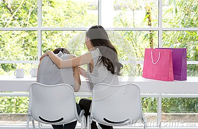 Sad woman sitting in the room. Friends do not give up. Sad girl and supporting friends to solve a problem. Stock Photo