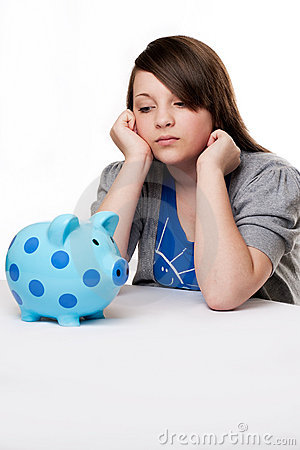 Sad young girl with piggy bank