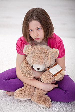 Sad young girl sitting with teddy bear