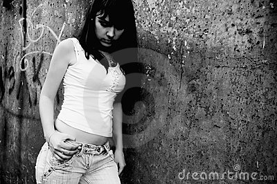 Sad young girl is standing at the wall