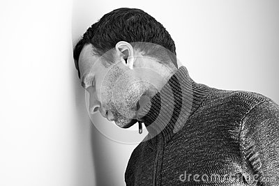 Sad young man rested his head on wall