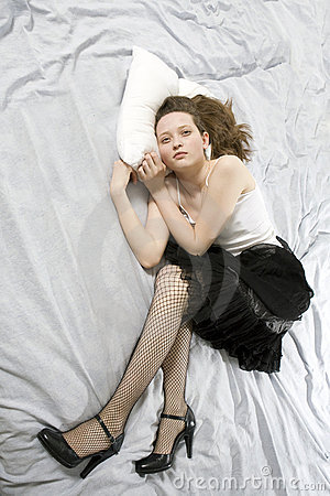 Sad young woman lying down on bed