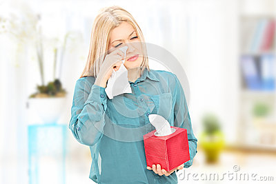 Sad young woman wiping her eyes at home