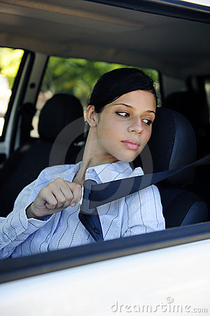 Safety: female driver fastening seat belt