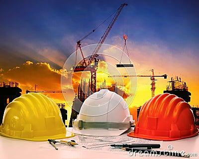 Safety helmet on civil engineer working table against crane lift