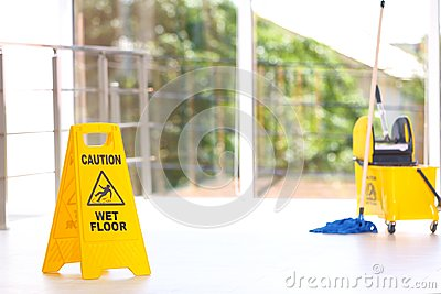 Safety sign with phrase Caution wet floor mop bucket, indoors. Cleaning service Stock Photo
