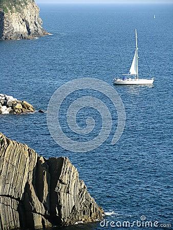 Sailboat along a Rocky Coast