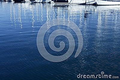 Sailboat blurred mast reflexion on the marina