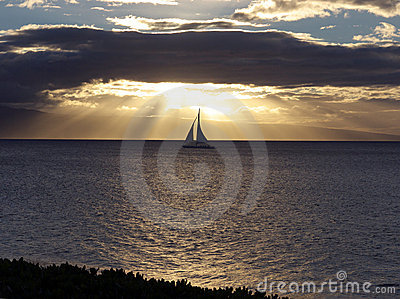 Sailboat gliding at sunset