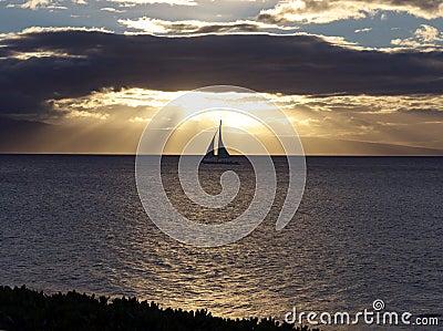 Sailboat gliding at sunset