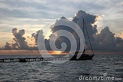 Sailboat moored at sunset