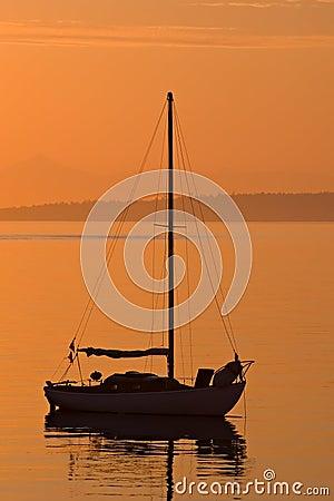 Sailboat silhouette during orange sunrise