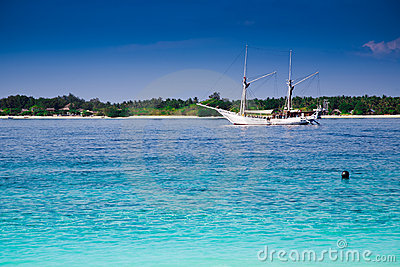 Sailboat at a turquoise tropic island