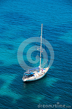 Sailing boat in blue water bay