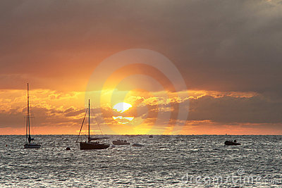 Sailing boats on horizon bathed in sun s rays