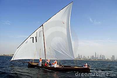 Sailing Dhow Against The Distant Cityscape Of Duba