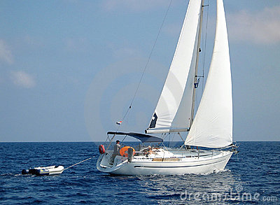 Sailboat sailing with dinghy