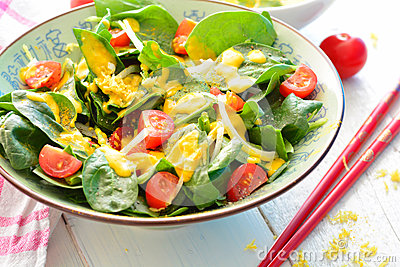 Salad with spinach, onions, tomatoes and a yellow turmeric dressing Stock Photo