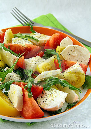 Salad with tomato and cheese arugula and olive oil