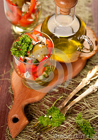 Salad of tomatoes, cucumbers and sweet peppers and a bottle of olive oil