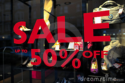 Sale (up to 50  off) sign in a fashion shop window