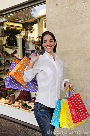 Sale: woman with shopping bags in front of a store
