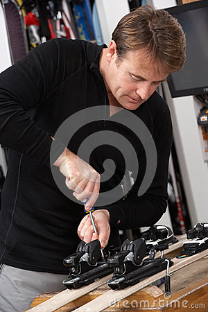 Sales Assistant Adjusting Fittings On Skis