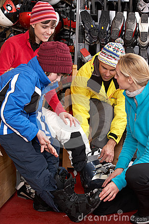 Sales Assistant Helping Family To Try On Ski Boots