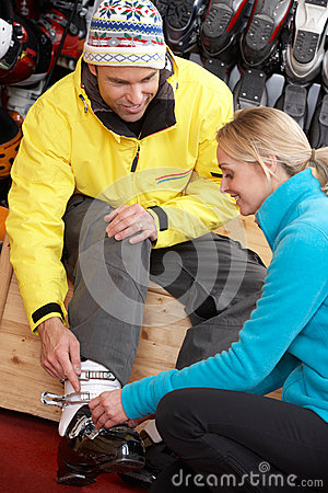 Sales Assistant Helping Man To Try On Ski Boots