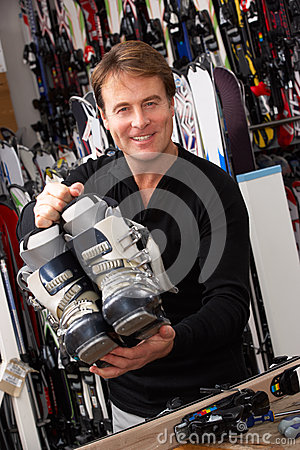 Free Sales Assistant With Ski Boots In Hire Shop Stock Photography - 25646102