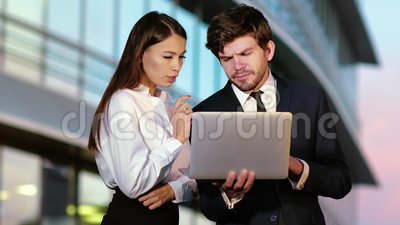 Sales people working on a laptop outside. Professional shot in 4K resolution. 029. You can use it e.g. in your commercial video, medical, business stock footage