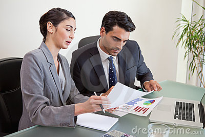 Sales persons working with a notebook