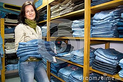 Saleslady na loja do desgaste das calças de brim