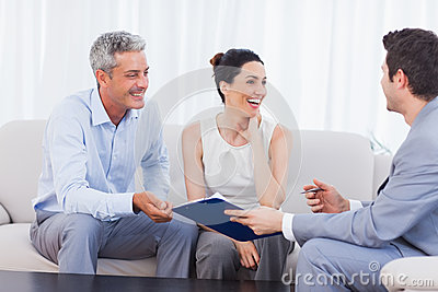 Salesman and clients talking and laughing together on sofa