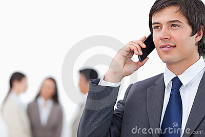 Salesman on his cellphone with team behind him