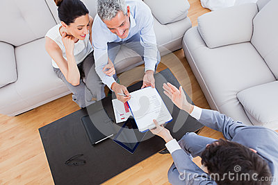 Salesman showing contract to couple who are about to sign