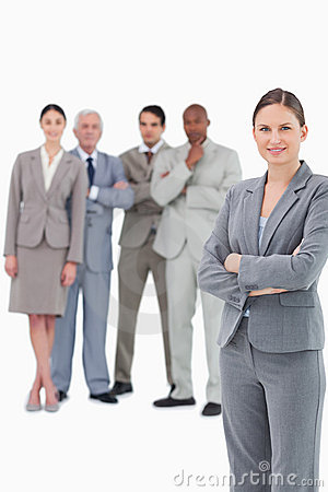 Saleswoman with arms folded and her team behind her