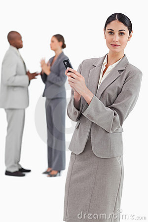 Saleswoman holding cellphone with colleagues behind her