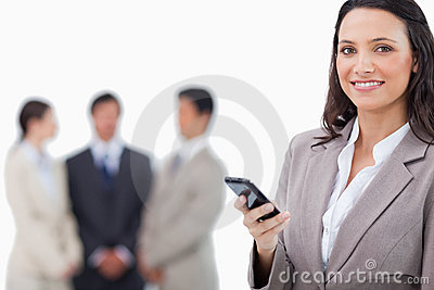 Saleswoman holding cellphone with team behind her