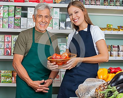Saleswoman Holding Vegetable Basket With Male