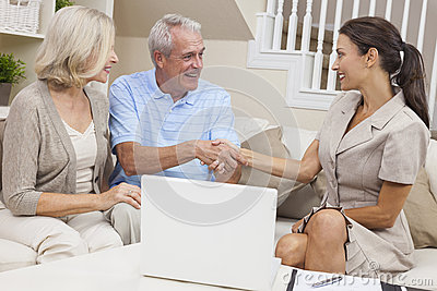 Saleswoman Shaking Hands With Senior Couple