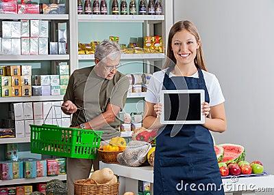 Saleswoman Showing Digital Tablet While Senior Man