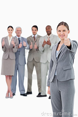 Saleswoman with thumb up and her team behind her