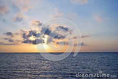 Salida del sol azul del océano en el tiempo nublado