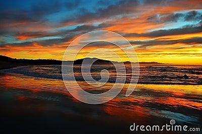 Salida del sol colorida del océano en la playa de Nahoon