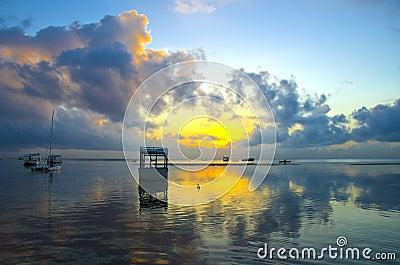 Salida del sol con el cielo y los barcos dramáticos
