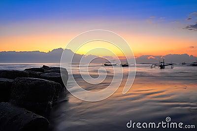 Salida del sol de la costa del océano y barcos blury